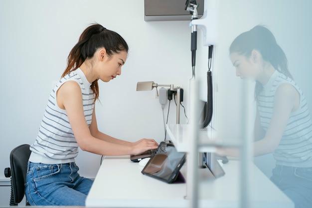 Médico chino mujer archivando archivos en la computadora del hospital. clínica veterinaria blanca limpia.