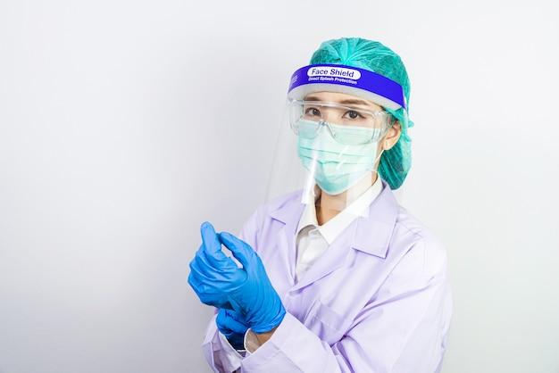 Médico científico con mascarilla, anteojos o gafas protectoras y traje protector para luchar contra la pandemia de coronavirus covid-19, cuarentena de amenaza pandémica de coronavirus, concepto médico y de atención médica.
