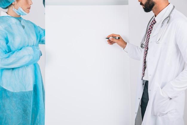 Médico y cirujana escribiendo en la pizarra blanca