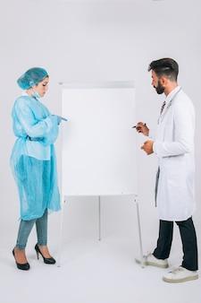 Médico y cirujana en una presentación con pizarra blanca