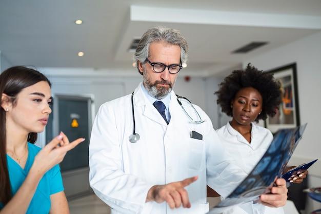El médico y el cirujano examinan la película de rayos x, diagnostican la lesión de la tomografía computarizada del paciente