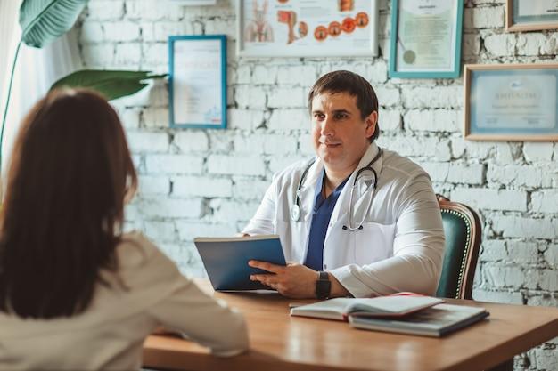 Médico cirujano masculino en uniforme médico con estetoscopio que tiene la consulta con un paciente atractivo en el gabinete.