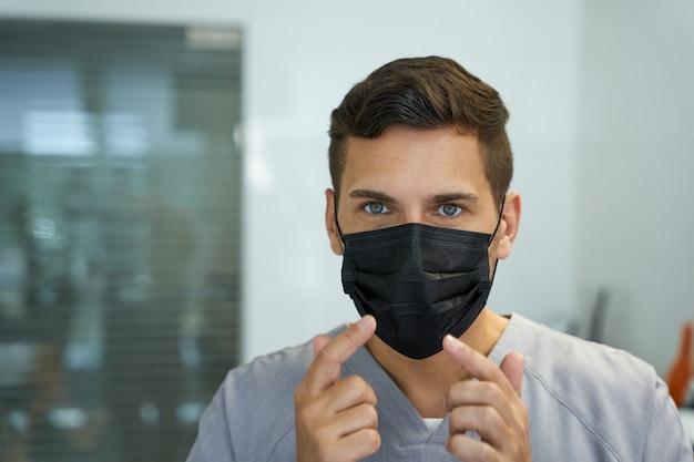 Médico consciente que muestra una forma correcta de usar una máscara
