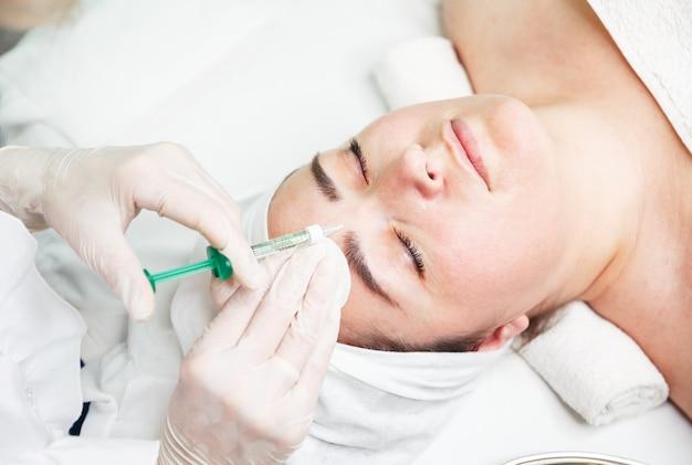 Médico cosmetólogo haciendo inyecciones biorevitalización en clínica