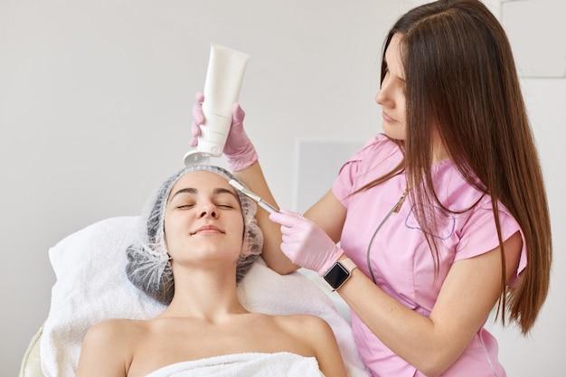 Médico cosmetólogo haciendo masaje de estiramiento facial para joven mujer morena, cliente acostado en los ojos cerrados, con una toalla blanca y gorra médica.