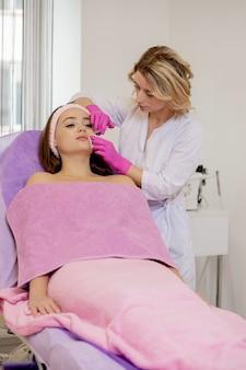 El médico cosmetólogo realiza las inyecciones faciales rejuvenecedoras.