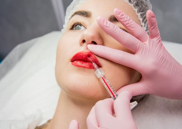 El médico cosmetólogo realiza el procedimiento de inyecciones faciales. mujer joven en un salón de belleza.