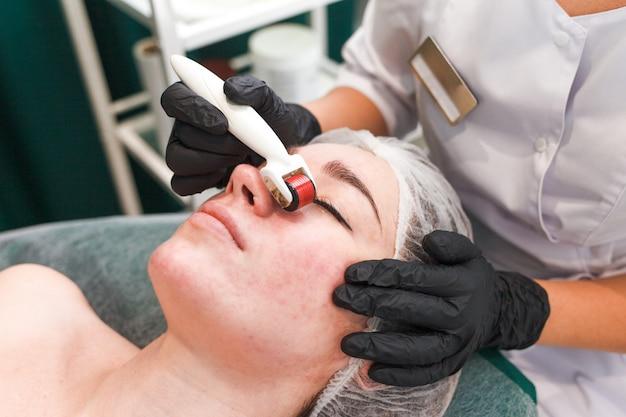 Médico cosmetólogo realiza un procedimiento de masaje facial con un rodillo dermo