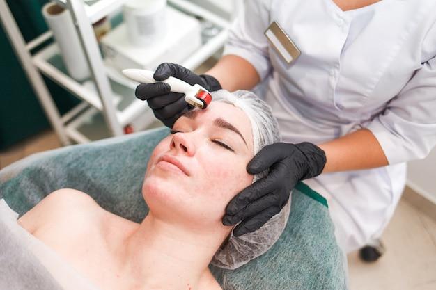 El médico cosmetólogo realiza un procedimiento de masaje facial utilizando un rodillo dermo. mujer en salón de belleza durante el procedimiento de mesoterapia con mesoscooter