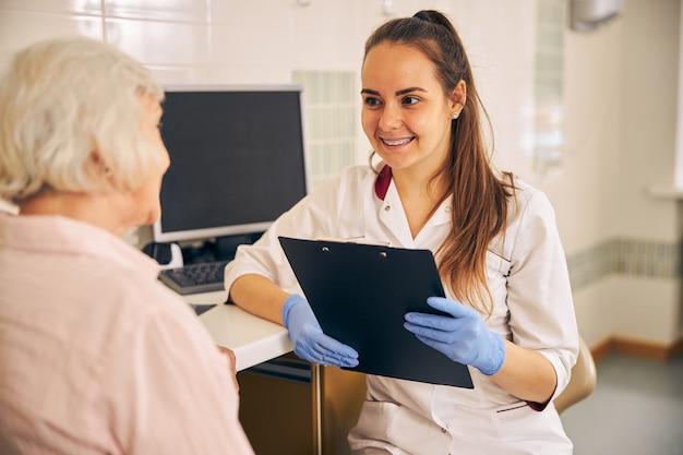 Médico cosmetólogo seguro que trabaja con documentos en la oficina de cosmética moderna mientras habla con el paciente