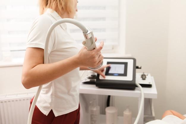 El médico cosmetólogo tiene en sus manos un dispositivo para masaje al vacío anticelulítico