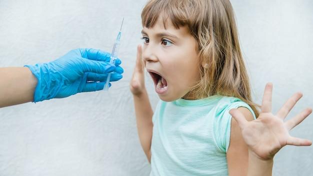 El médico le da al niño una inyección en el brazo.