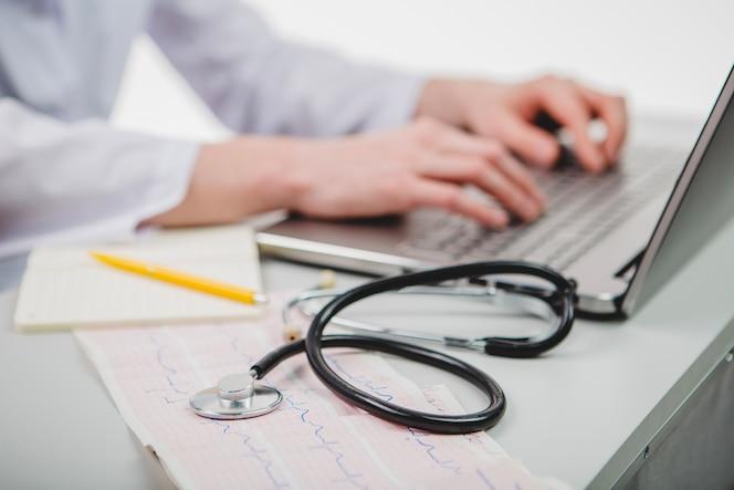 Médico de cultivos escribiendo portátil
