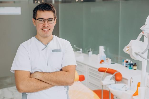 Médico dental de pie en la clínica