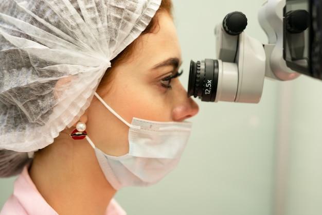 Médico dentista joven mira a través de un microscopio profesional en una clínica dental