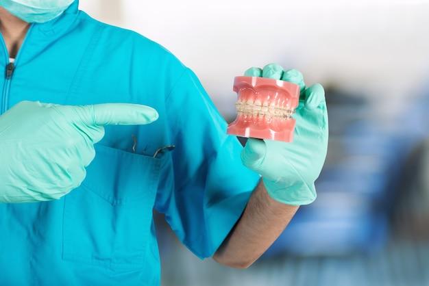Médico dentista muestra cómo aplicar un aparato ortopédico