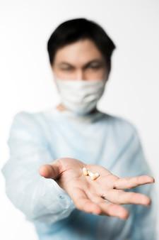 Médico desenfocado con máscara médica con pastillas en la mano