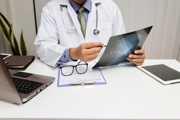El médico diagnostica y analiza la película de rayos x del paciente.