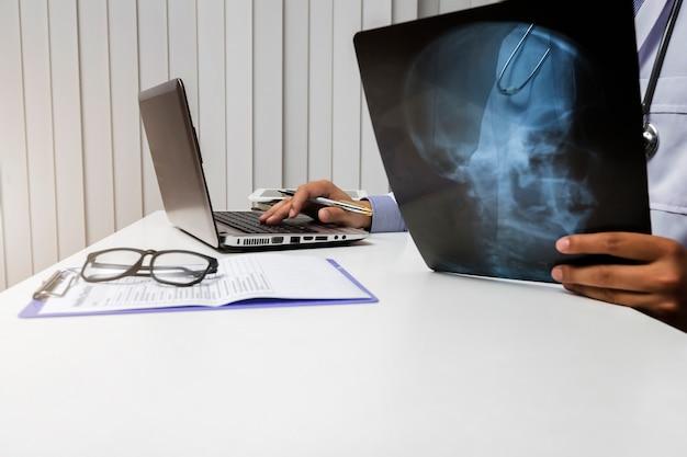 Médico diagnostica y analiza en radiografía de paciente.