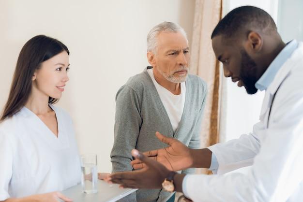 El médico le dice a la enfermera cómo un hombre anciano debe tomar pastillas
