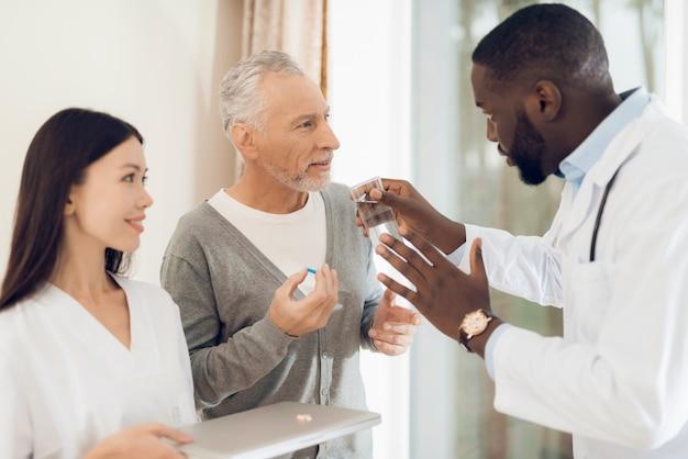 El médico le dice a la enfermera cómo un paciente anciano debe tomar pastillas