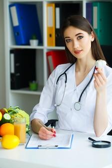 El médico dietista lo sostiene en las manos del ajo.