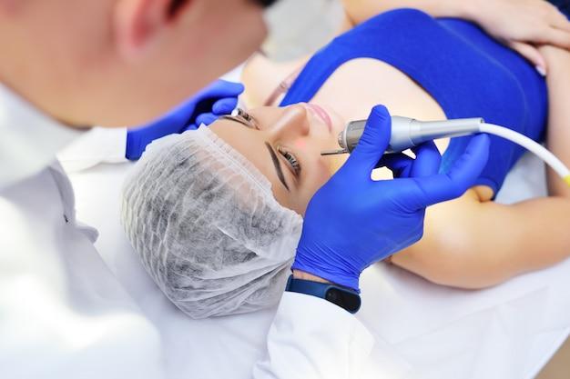 El médico elimina los lunares de pigmentación o las verrugas del paciente con láser de neodimio.