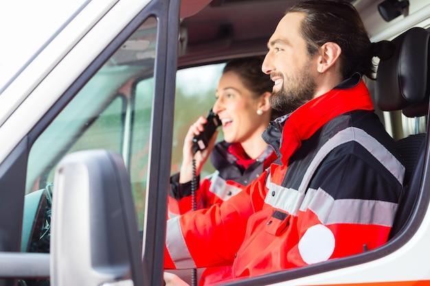 Médico de emergencia y enfermera conduciendo una ambulancia.