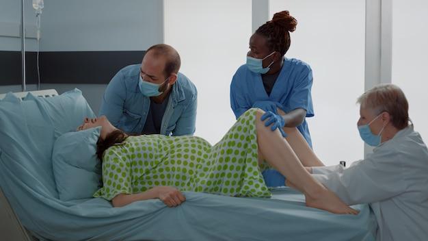 Médico y enfermera afroamericana dando a luz al bebé