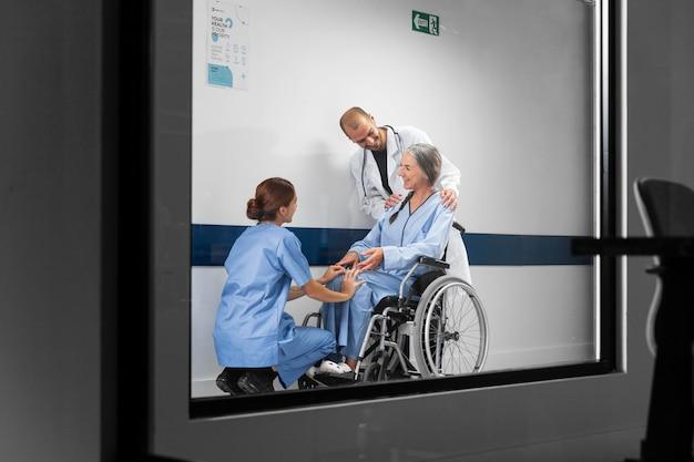 Médico y enfermera ayudando al paciente en silla de ruedas