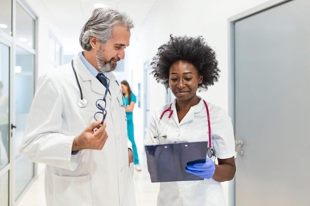 Médico y enfermera discutiendo sobre un informe médico en el hospital.