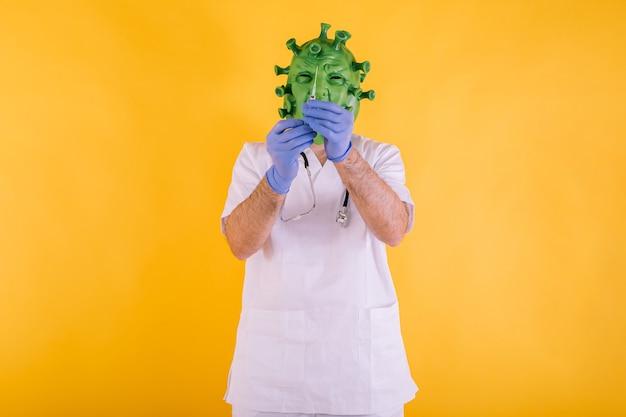 Médico - enfermera disfrazada de coronavirus con máscara de látex - virus covid-19 con una jeringa con agua en las manos sobre fondo amarillo. concepto de coronavirus