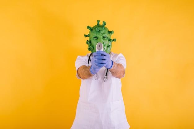 Médico enfermera disfrazado de coronavirus con máscara de látex virus covid apuntando con un termómetro electrónico sobre fondo amarillo concepto de coronavirus