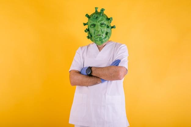 Médico enfermera disfrazado de coronavirus con máscara de látex virus covid con brazos cruzados sobre fondo amarillo concepto de coronavirus