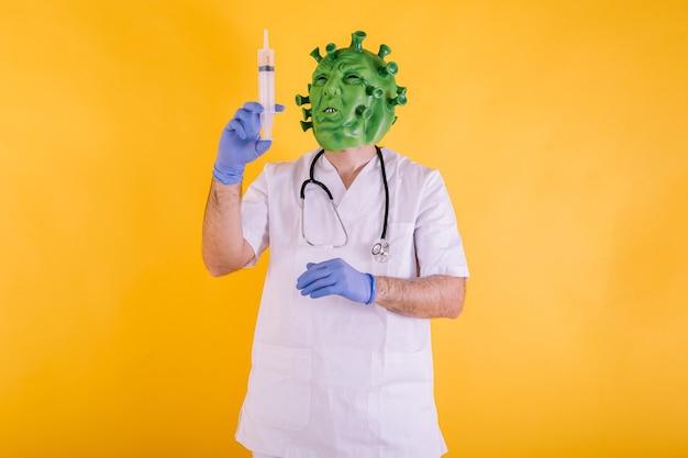 Médico enfermera disfrazado de coronavirus con máscara de látex virus covid con una jeringa en sus manos sobre fondo amarillo concepto de coronavirus