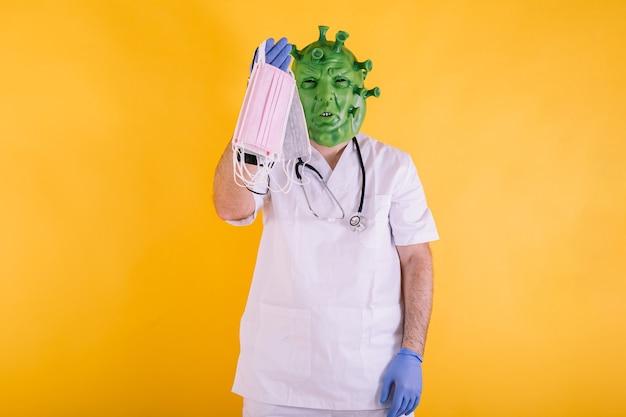 Médico enfermera disfrazado de coronavirus con máscara de látex virus covid con máscaras quirúrgicas en la mano sobre fondo amarillo concepto de coronavirus