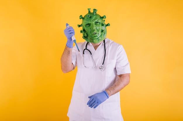 Médico enfermera disfrazado de coronavirus con máscara de látex virus covid con una pipeta de laboratorio en sus manos sobre fondo amarillo concepto de coronavirus