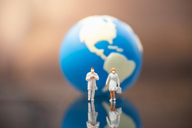 Médico y enfermera figura en miniatura personas caminando con mini bola mundial como fondo.