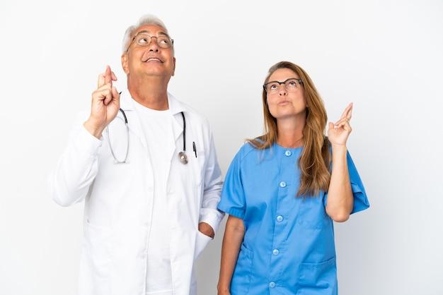 Médico y enfermera de mediana edad aislado sobre fondo blanco con los dedos cruzados y deseando lo mejor