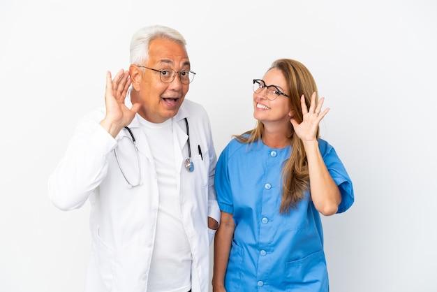 Médico y enfermera de mediana edad aislado sobre fondo blanco escuchando algo poniendo la mano en la oreja