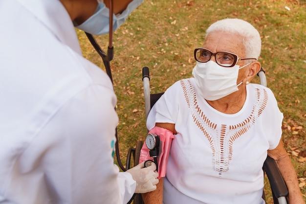 Médico enfermera midiendo la presión de la anciana
