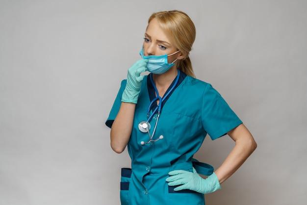 Médico enfermera mujer con máscara protectora y guantes de goma o látex - cansados y estresados
