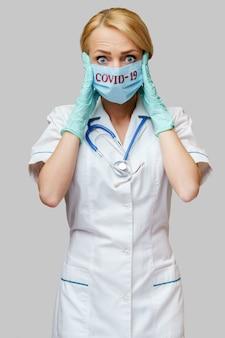Médico enfermera mujer con máscara protectora y guantes de goma o látex - dolor de cabeza y estrés