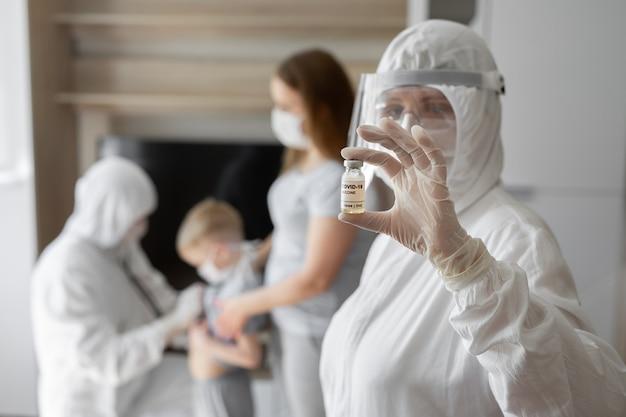 Médico, enfermera o científico de la mano en guantes de nitrilo blanco con vacuna contra el coronavirus para la vacunación de bebés y adultos, medicamentos para el tratamiento del virus covid-19