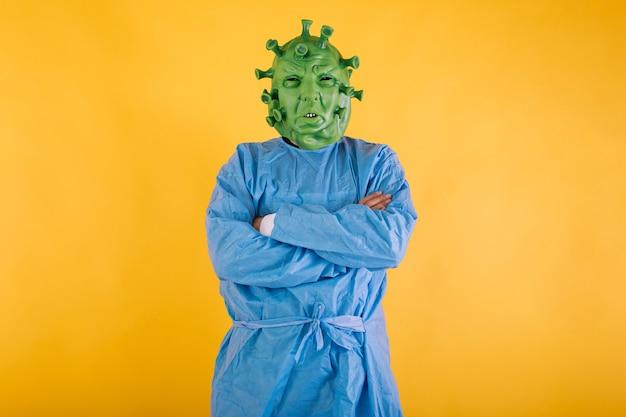 Médico enfermera con un ppe disfrazado de coronavirus con máscara de látex virus covid con brazos cruzados sobre fondo amarillo concepto de coronavirus