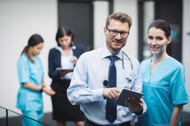 Médico y enfermera sonriente con tableta digital