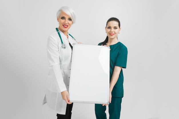Médico y enfermera sosteniendo un tablero magnético vacío aislado sobre fondo blanco.