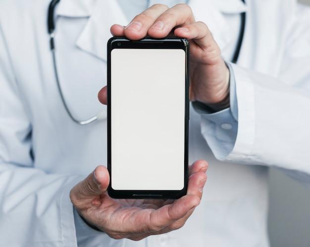 Médico enseñando un teléfono móvil