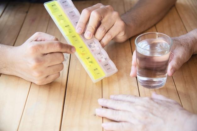El médico es ayudar al paciente a comer la tableta de medicina en el pastillero correctamente