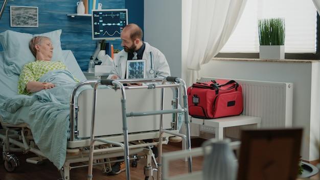 Médico con escaneo de rayos x en tableta para paciente enfermo jubilado